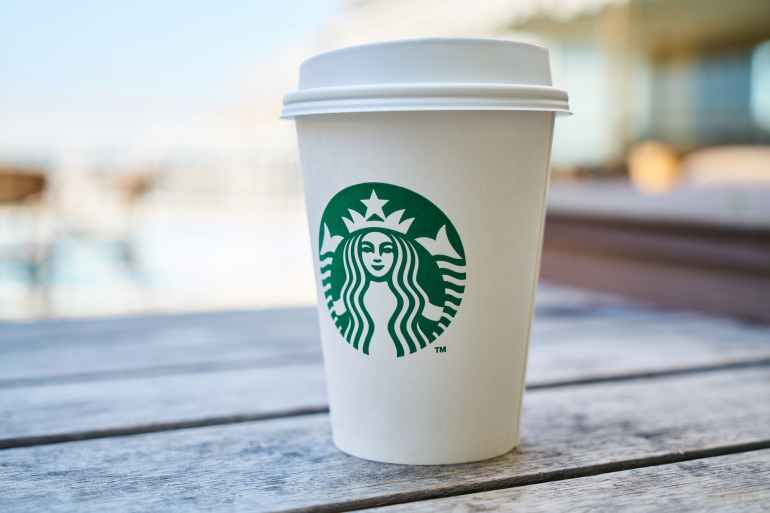 closed white and green starbucks disposable cup